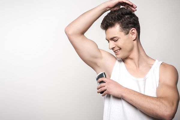 smiling man in white sleeveless shirt applying deodorant on underarm isolated on grey