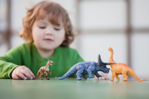 toddler kid having fun playing with a toy dinosaur, horizontal natural light photo